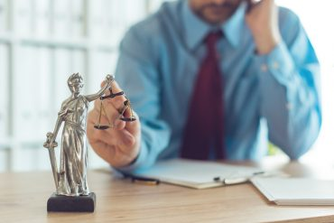Attorney talking on mobile device and playing with Justice scale in law office, selective focus on statue of Lady Justice