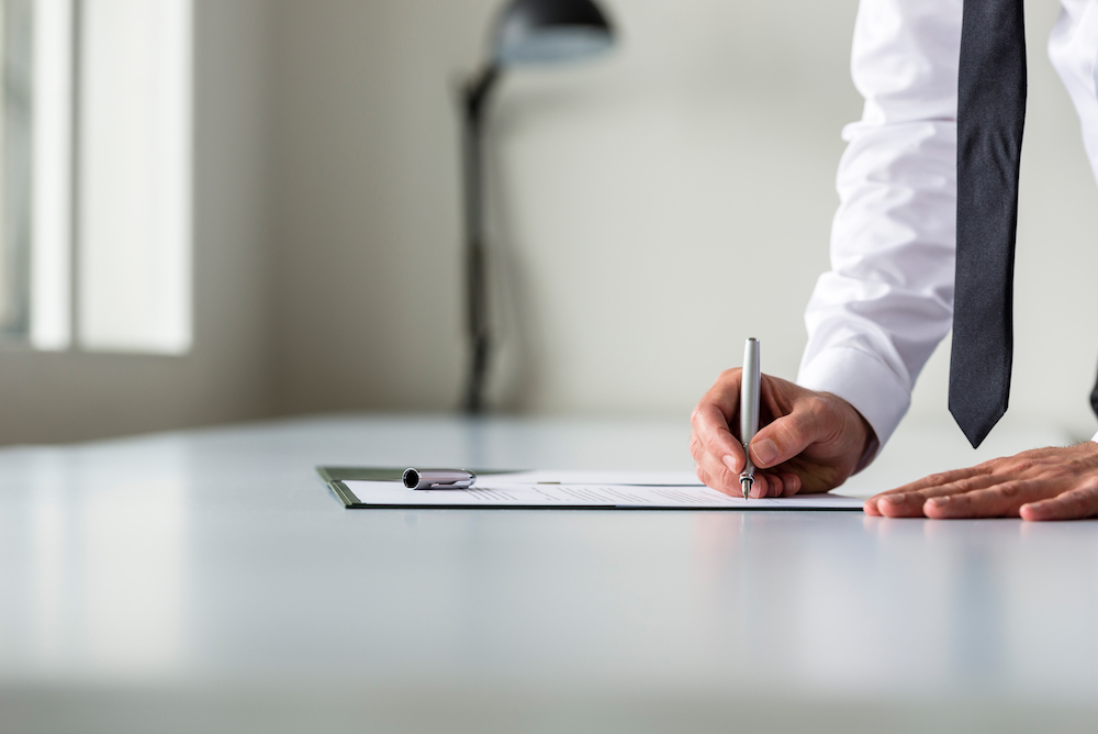 Man in white shirt signing contract or subscription form with a pen on an office desk.