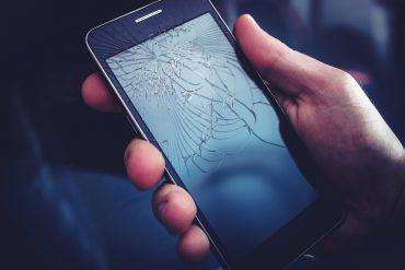Broken Smartphone Display. Crashed Cellphone in Hand.