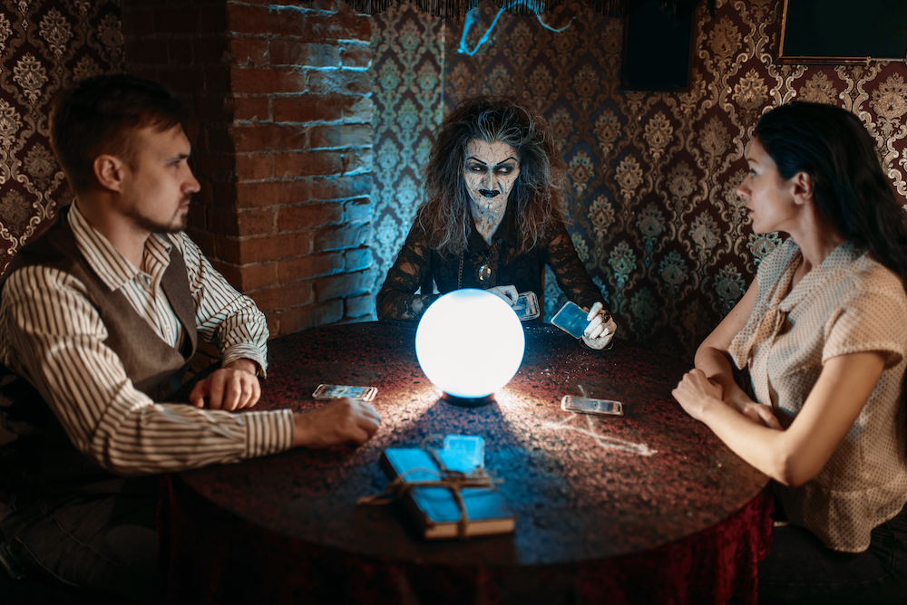 Scary witch reads a magic spell over a crystal ball, young man and woman on spiritual seance. Female foreteller calls the spirits
