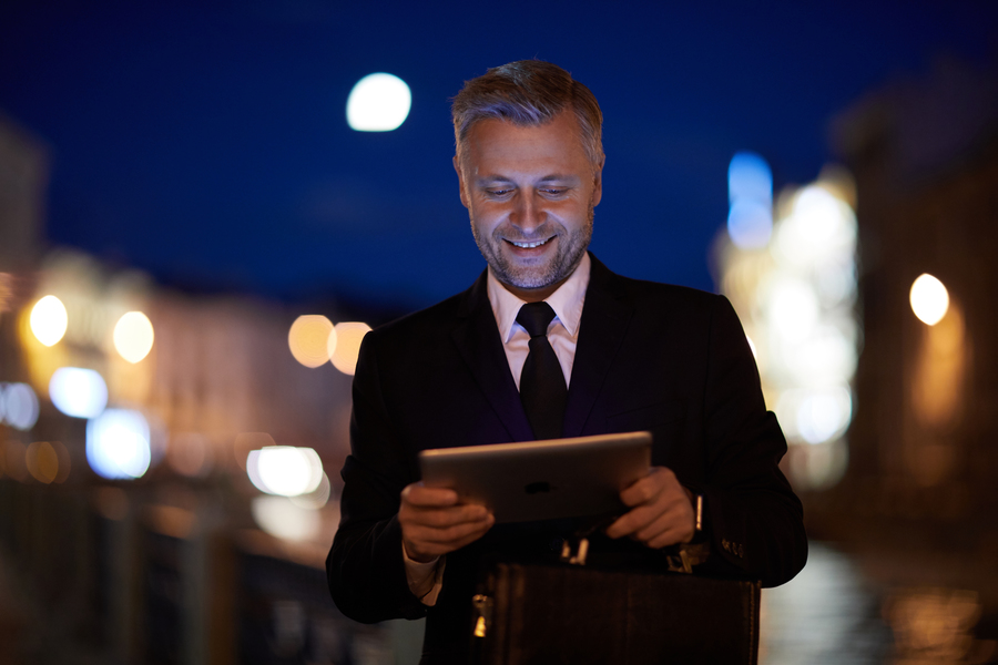 Young successful businessman with mobile gadget reading online news in urban environment