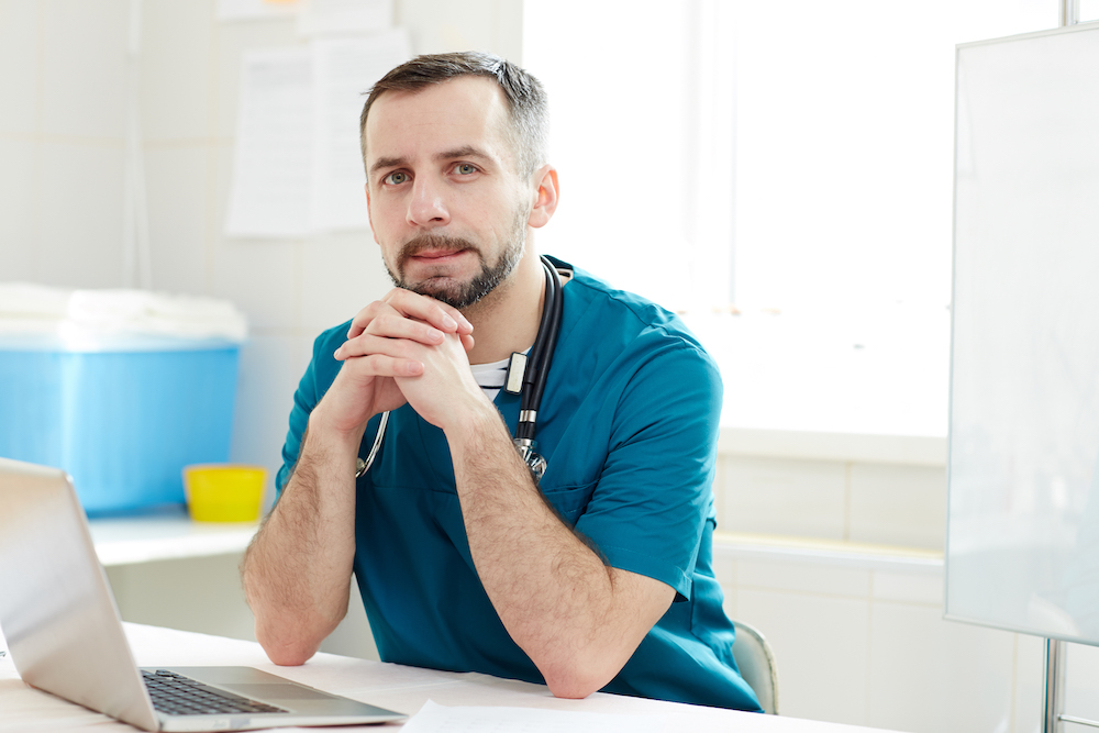 Young serious doctor in uniform looking at camera while sitting by workplace in front of laptop