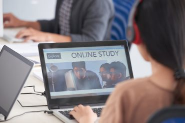 Young woman watching online course on her laptop