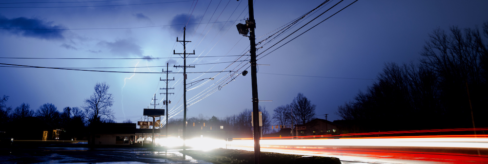 Traffic moves by under the electrical storm, lighting, light and energy coming from all around
