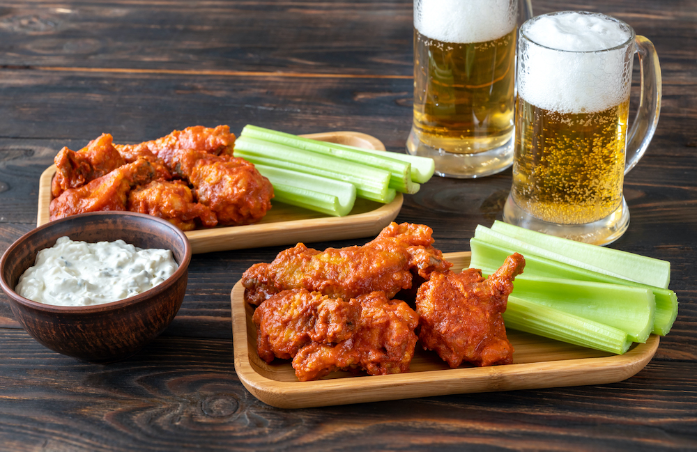 Buffalo wings with celery stalks, blue cheese dip and glass mugs of beer