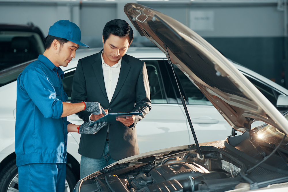 Vietnamese car service worker and client discussing work and signing document