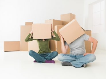 couple with boxes on their heads sitting on floor in their new house, feeling stressed